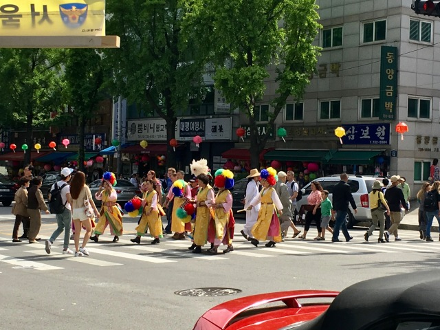 People crossing the street in front of the temple, presumably getting ready for the parade.